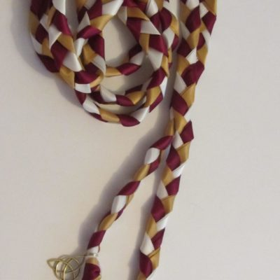 Elegant burgundy, gold and ivory braid with antique gold Celtic charm.